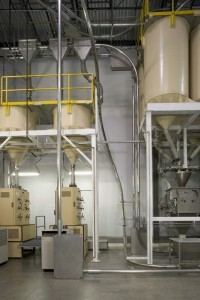 The roasted beans discharge from the holding silos (right) into a conveying system that moves them vertically and then horizontally above the two grinders (bottom left).